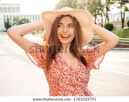 Portrait of young beautiful smiling hipster girl in trendy summer sundress.Sexy carefree woman posing on the street background in hat at sunset. Positive model outdoors