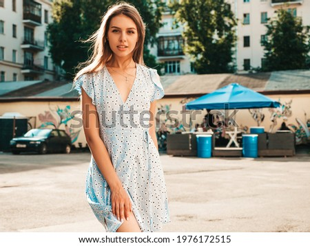 Portrait of young beautiful smiling  woman in trendy summer sundress.Sexy carefree woman posing on the street background at sunset. Positive model outdoors