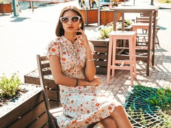 Portrait of young beautiful smiling  woman in trendy summer sundress.Sexy carefree woman sitting in veranda cafe on the street background at sunset. Positive model outdoors in sunglasses