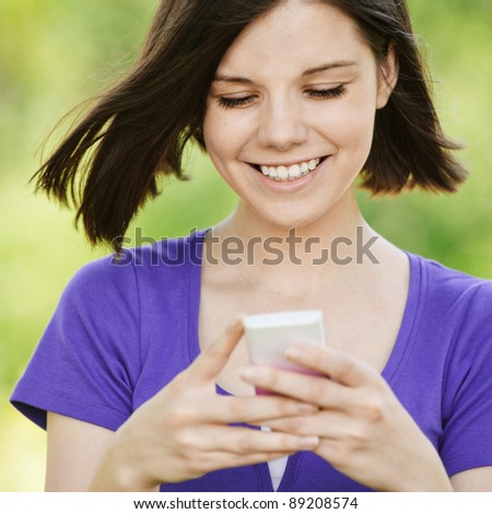 Portrait of young beautiful smiling woman wearing violet blouse with mobile phone at summer green park.