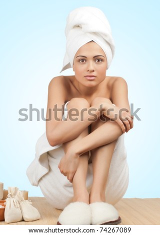 Portrait of young beautiful spa woman sitting on bamboo mat at spa salon. Isolated on blue background.