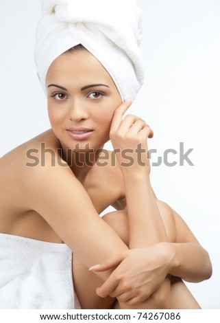 Portrait of young beautiful spa woman wearing white towel. Isolated on white background.