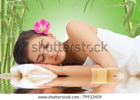 Portrait of young beautiful spa woman with flower in her hair lying and relaxing