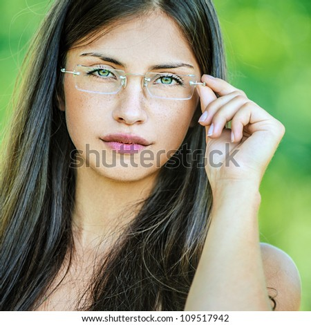 Portrait of young beautiful woman adjusts glasses, on green background summer nature.