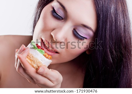 Portrait of young beautiful woman eating cake on a white background. Enjoy the food. Brunette with fashion pink makeup with false eyelashes.