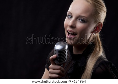 portrait of young beautiful woman holding retro microphone
