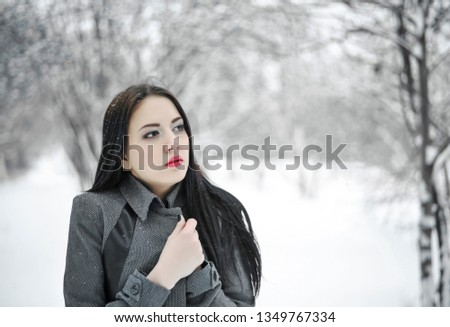 Portrait of young beautiful woman in coat enjoing the first snow. Stunning skinny brunette with a gorgeous brunette hair in the winter forest during the snowfall #1349767334