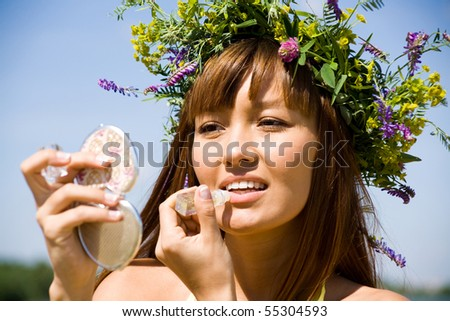 Portrait of Young beautiful woman in floral wreath uses lipstick