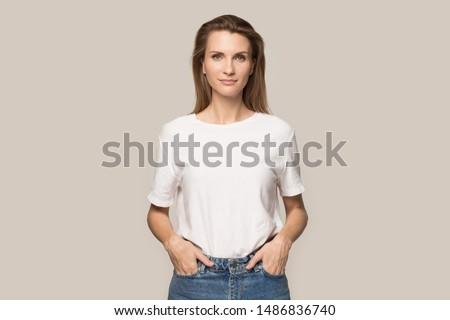 Portrait of young beautiful woman in jeans and T-shirt hold hands in pockets look at camera pose for picture, pretty millennial Caucasian female model with long hair isolated on grey studio background