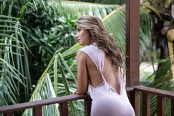 Portrait of young beautiful woman in pink dress with open back on balcony of tropical bungalow with palm trees view in Bali