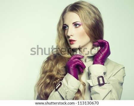 Portrait of young beautiful woman in purple gloves. Fashion photo
