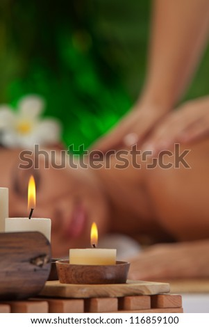 portrait of young beautiful woman in spa environment. blurred face, focused on candles.