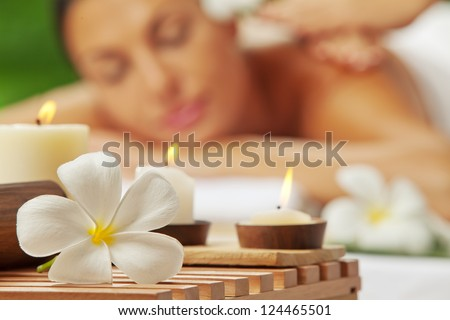 portrait of young beautiful woman in spa environment. blurred face, focused on flower.