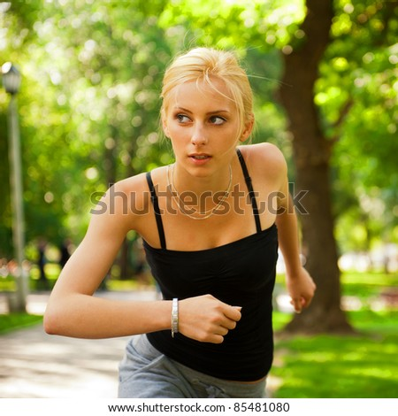 Portrait of young beautiful woman in sportswear running in park. Outdoors. Horizontal shot
