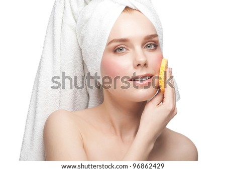 Portrait of young beautiful woman in white towel with bath sponge cleaning her face. Isolated on white background