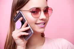 Portrait of young beautiful woman isolated on pink background in t-shirt of the same color. An attractive smiling girl speaks on mobile phone on which is attached modern holder for phone pop socket