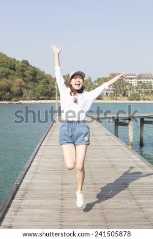 portrait of young beautiful woman jumping with happy emotion on wood piers at sea side use for people activities in holiday vacation