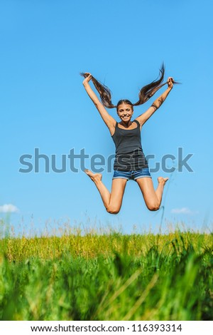 Portrait of young beautiful woman jumps high into sky, on green background summer nature.
