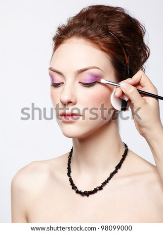 portrait of young beautiful woman maked up by makeup artist's hand putting on purple eyeshadow