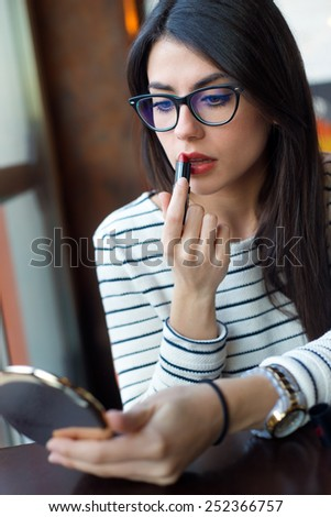 Portrait of young beautiful woman making up her face.