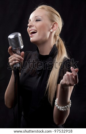 portrait of young beautiful woman singing with retro microphone