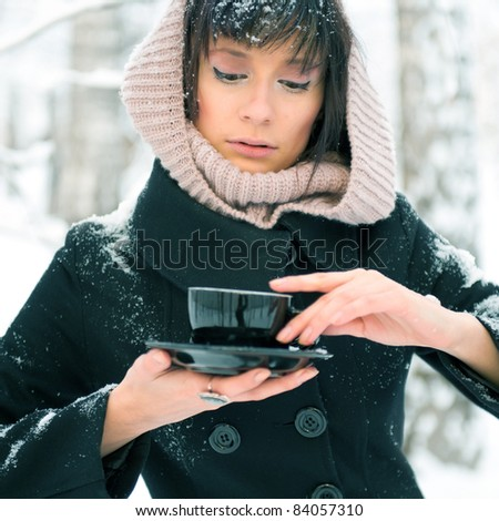 Portrait of young beautiful woman standing alone in winter park and drinking coffee. Take-away coffee as natural as it can be - concept. Advertisement banner