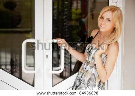 Portrait of young beautiful woman standing in front of door of her house and welcoming guests to visit her home. She is cute and friendly
