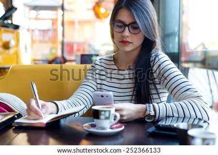 Portrait of young beautiful woman using her mobile phone in coffee. #252366133