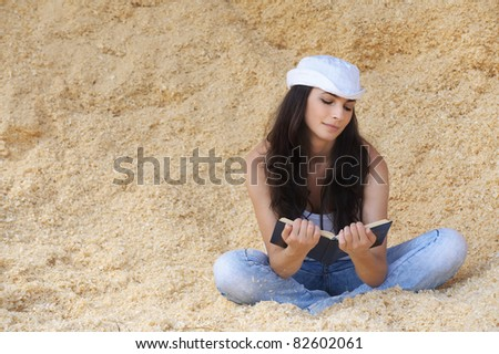 Portrait of young beautiful woman wearing white cap, t-shirt and jeans sitting in sawdust and reading book against yellow background.