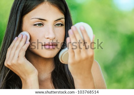 Portrait of young beautiful woman with bare shoulders causes powder to face, on green background summer nature.