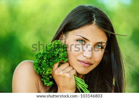 Portrait of young beautiful woman with bare shoulders holding bunch of parsley, on green background summer nature.