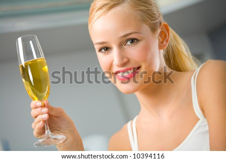 Portrait of young beautiful woman with champagne glass, indoors