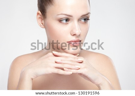 portrait of young beautiful woman with clean skin. On grey background