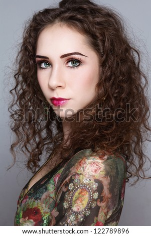 Portrait of young beautiful woman with curly hair and fancy make-up