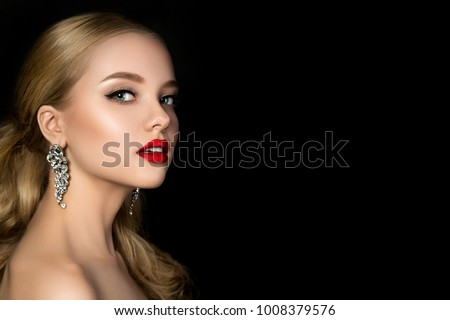 Portrait of young beautiful woman with evening make up looking over her shoulder. Model posing over dark background. Red lips and eyeliner. Classic makeup concept. Studio shot. Copy space
