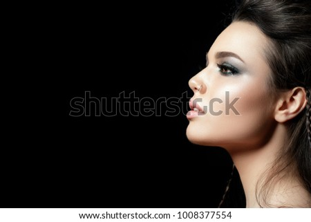 Stock Photo Portrait of young beautiful woman with evening make up. Model posing over black background. Silver smokey eyes. Classic makeup concept. Studio shot. Copy space
