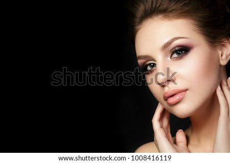 Portrait of young beautiful woman with evening make up touching her face over black background. Multicolored smokey eyes. Luxury skincare and modern fashion makeup concept. Studio shot. Copy space #1008416119