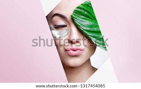 Portrait of young beautiful woman with healthy glow perfect smooth skin holds green tropical leaf, look into the hole of colored pink paper. Model with natural nude make up. Fashion, beauty, skincare.
