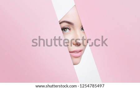 Portrait of young beautiful woman with healthy glow perfect smooth skin look into the hole of colored paper. Model with natural nude make up peers into hole in pink paper. Fashion, beauty, skincare.