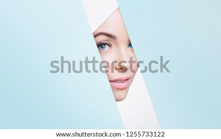 Portrait of young beautiful woman with healthy glow perfect smooth skin look into the hole of colored paper. Model with natural nude make up peers into hole in blue paper. Fashion, beauty, skincare. #1255733122