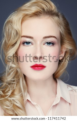 Portrait of young beautiful woman with long blond curly hair