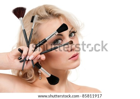 Portrait of young beautiful woman with makeup brushes over white background - stock photo