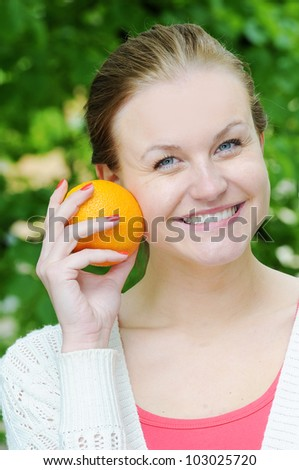 Portrait of young beautiful woman with orange