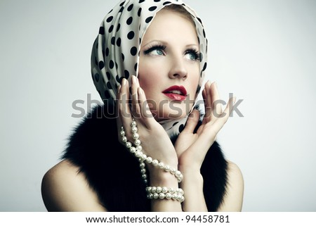 Portrait of young beautiful woman with pearl necklace. Fashion photo