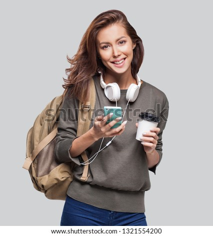 Portrait of young beautiful woman with smart phone and coffee. Smiling student girl going on travel. Studio shot isolated on gray background. Travel, student lifestyle, technology, connection concept