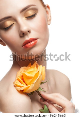 Portrait of young beautiful woman with stylish bright make-up with rose in her hand