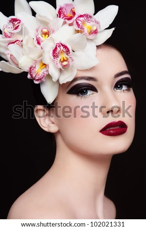 Portrait of young beautiful woman with stylish fancy make-up and orchids in her hair