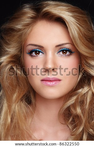 Portrait of young beautiful woman with stylish make-up and long curly fair hair