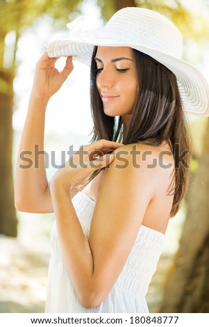 Portrait of young beautiful woman with white sun hat and white dress relaxing in the forest.