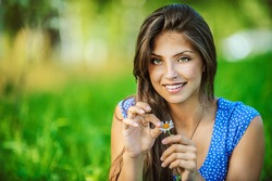 Portrait of young beautiful woman wonders, tearing petals on daisy, on green background summer nature.